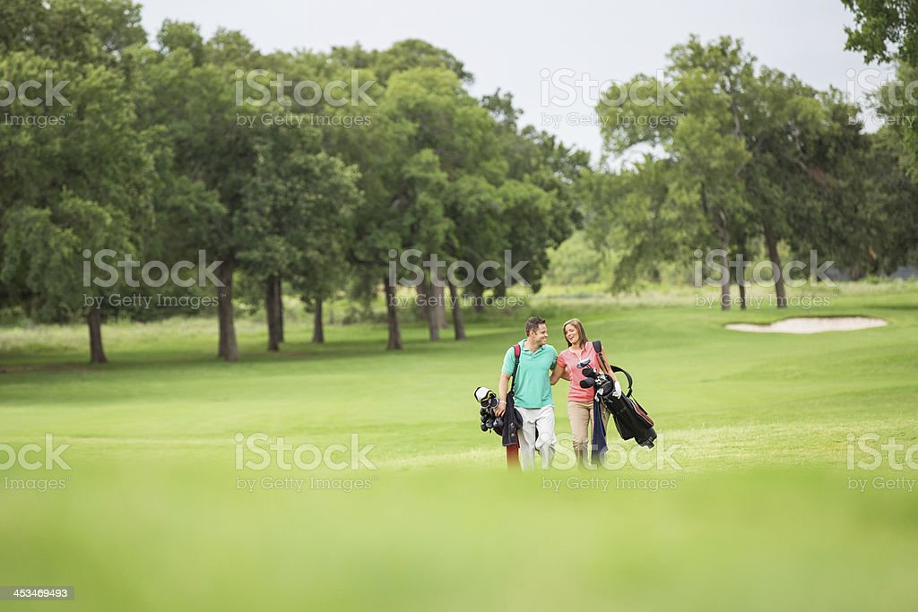 Couple carrying clubs walking on golf course together stock photo