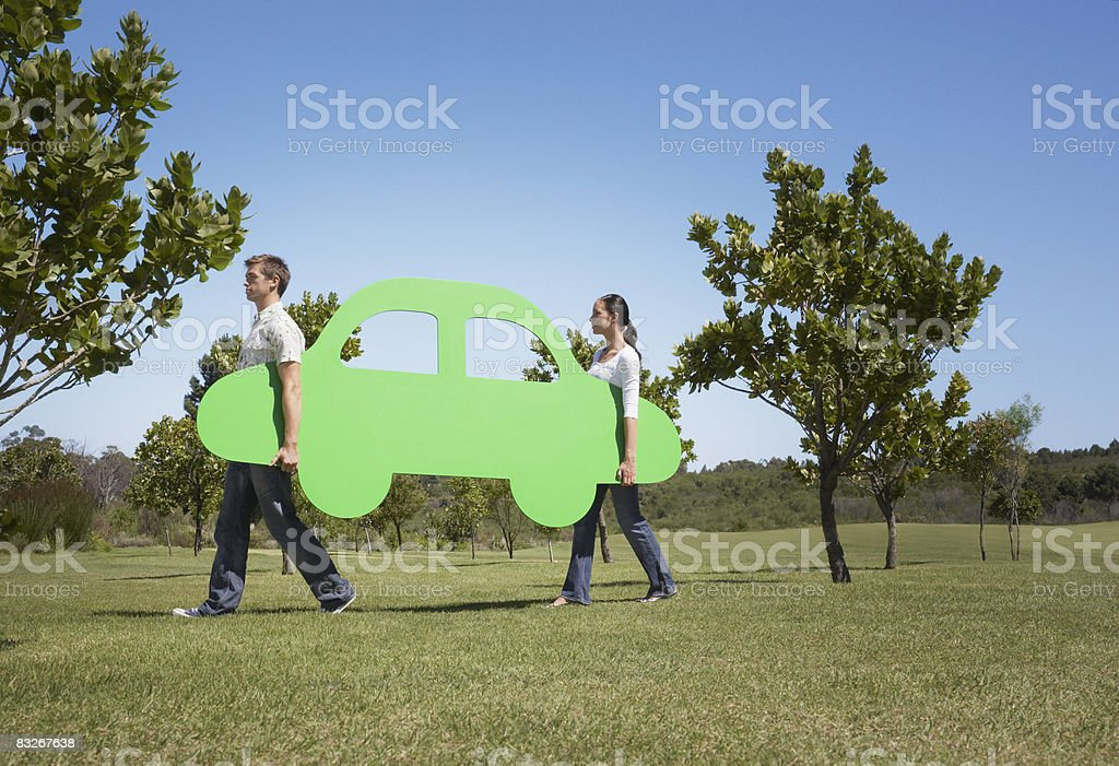Couple carrying cutout car through field stock photo
