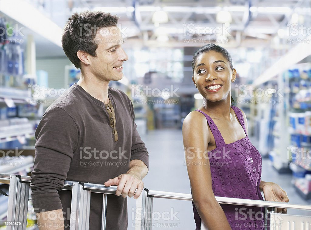 Couple carrying ladder through store royalty-free stock photo