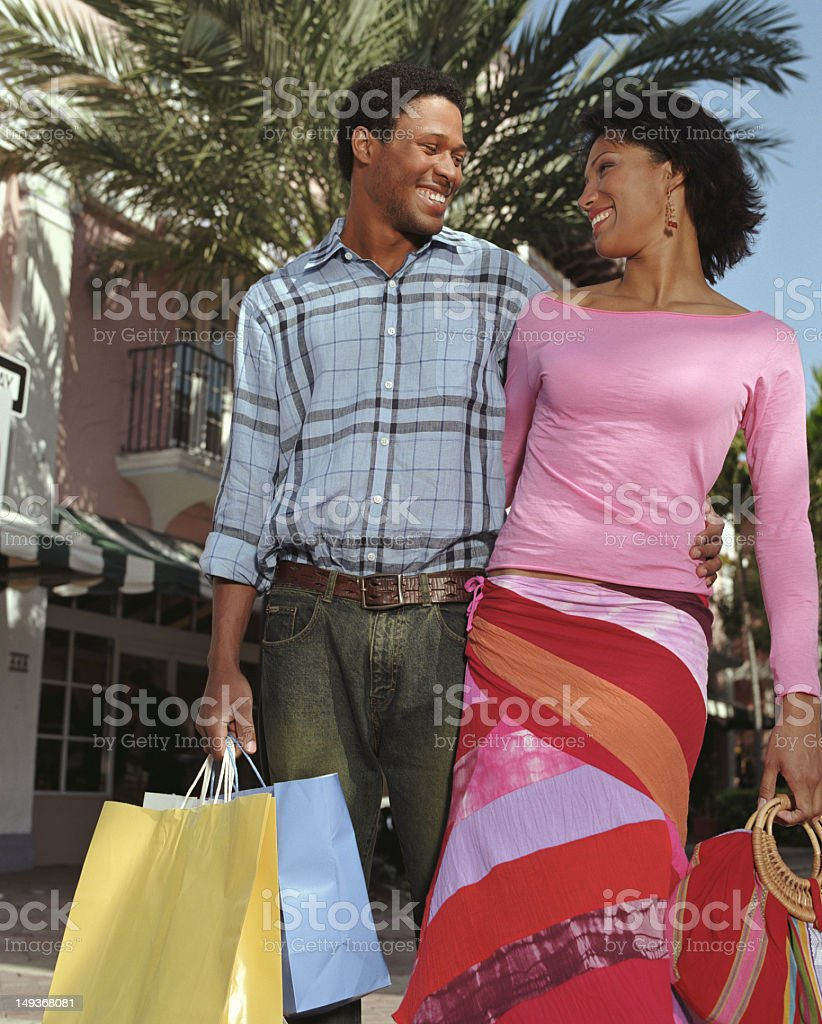 Couple carrying shopping bags embracing outdoors stock photo