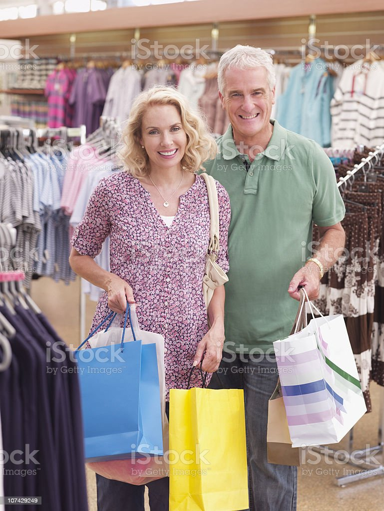Couple carrying shopping bags in store royalty-free stock photo