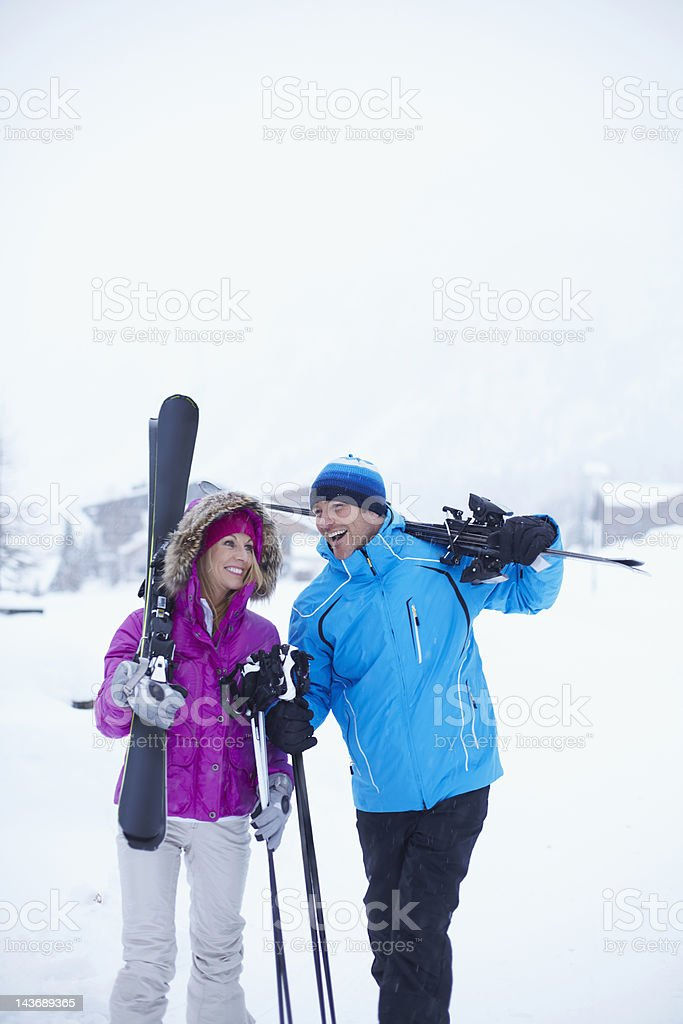 Couple carrying skis and poles in snow royalty-free stock photo