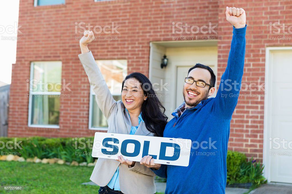 Couple celebrates in front of new home stock photo