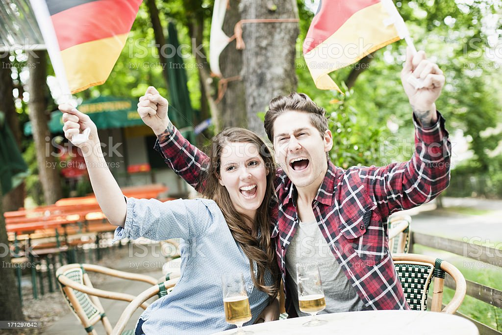 Couple celebrating Germany's sports victory at a country pub. royalty-free stock photo