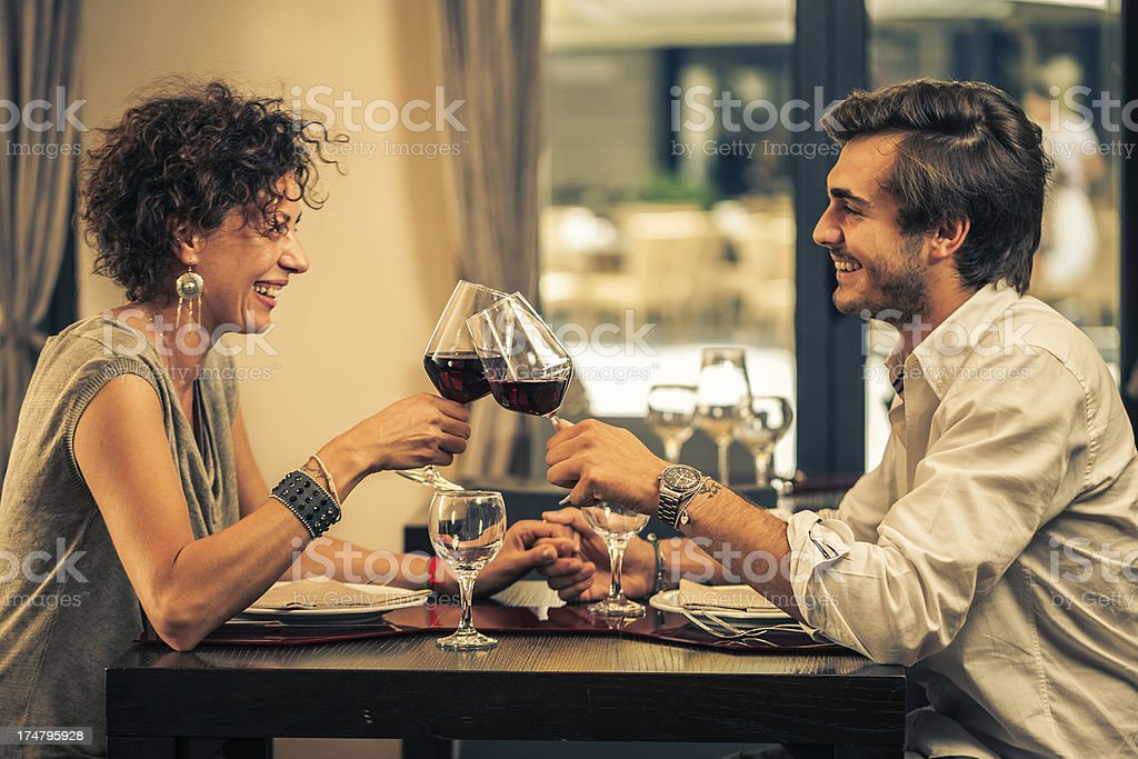 Couple celebrating with red wine at restaurant royalty-free stock photo