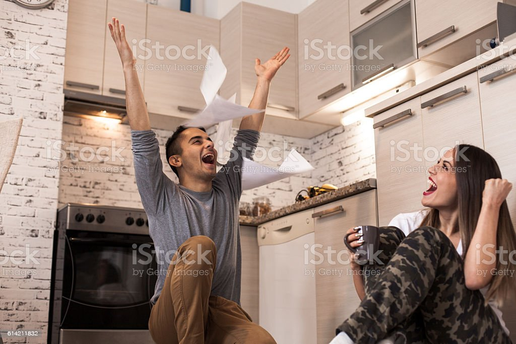 Couple celebrating with their arms raised. stock photo
