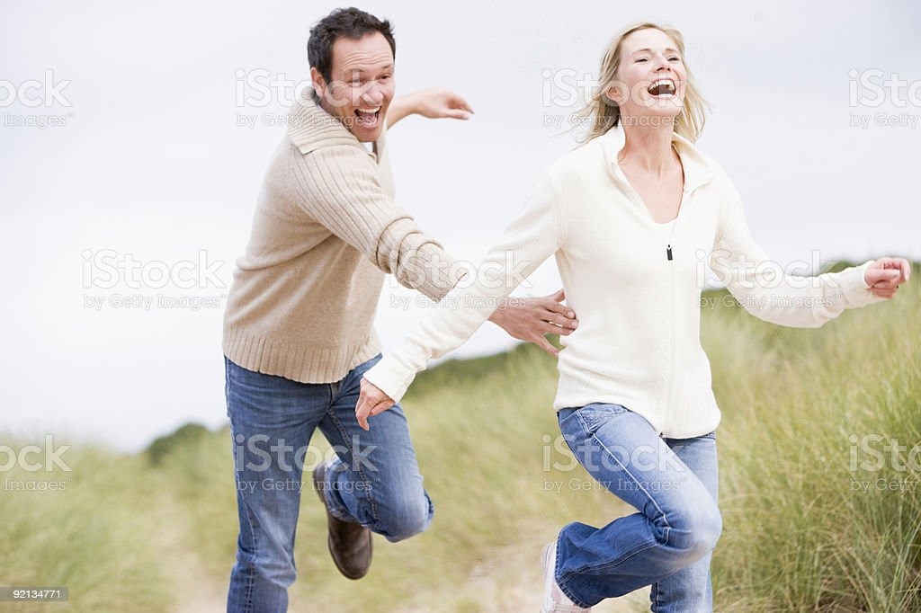 Couple chasing one another through dunes stock photo