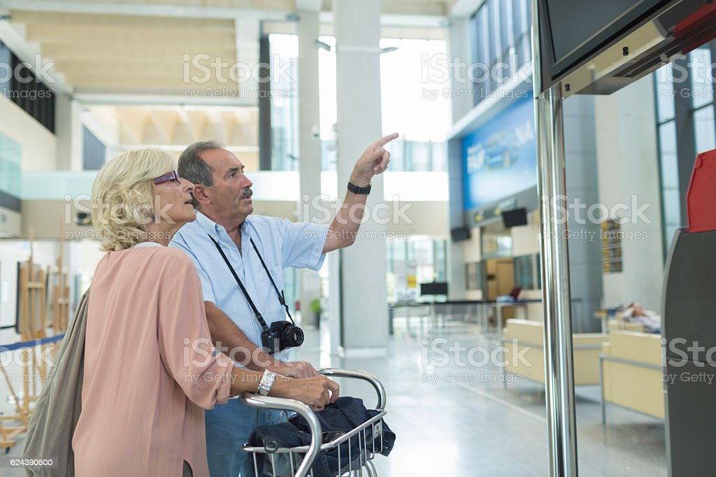 Couple chcecking for plane delay on departure panel stock photo