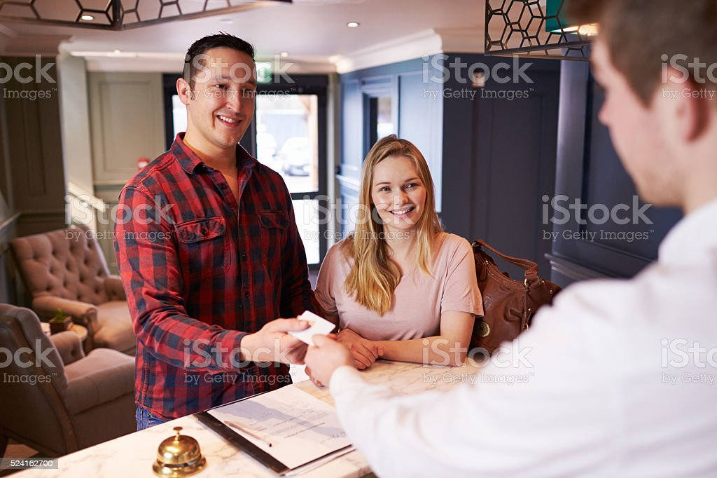 Couple Checking In At Hotel Reception Desk stock photo