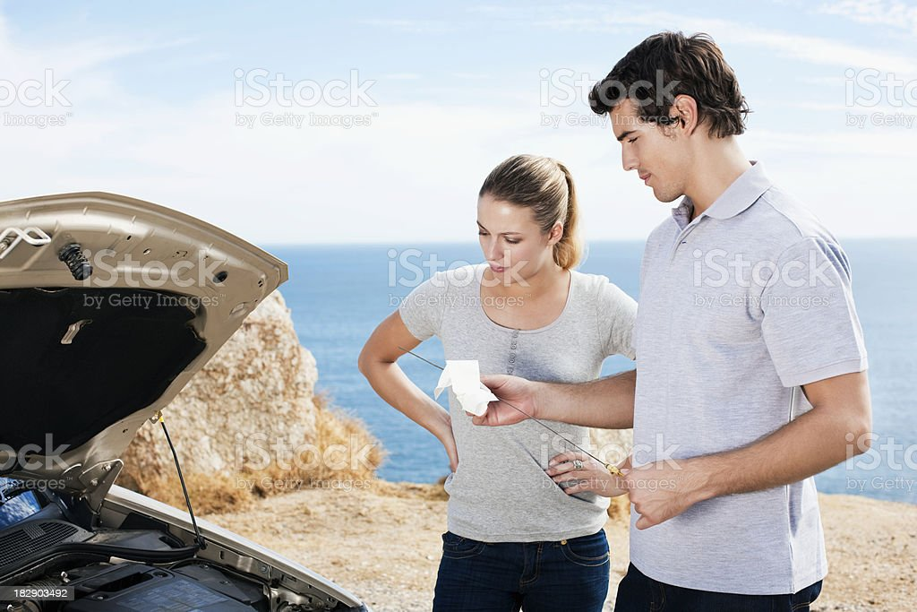 Couple Checking Oil royalty-free stock photo