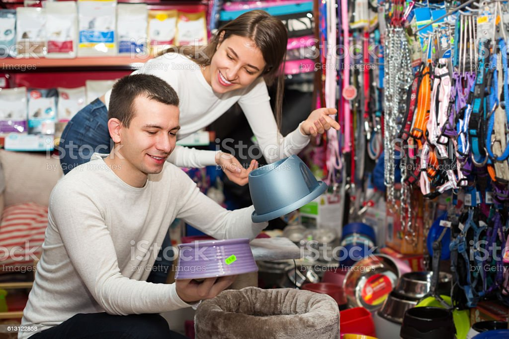 Couple choosing bowl in pet store stock photo