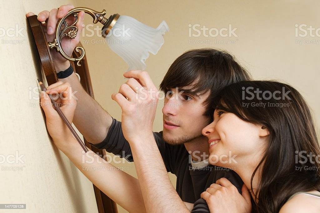 Couple choosing place for new lamp royalty-free stock photo
