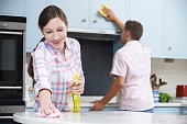 Couple Cleaning Kitchen Surfaces And Cupboards Together