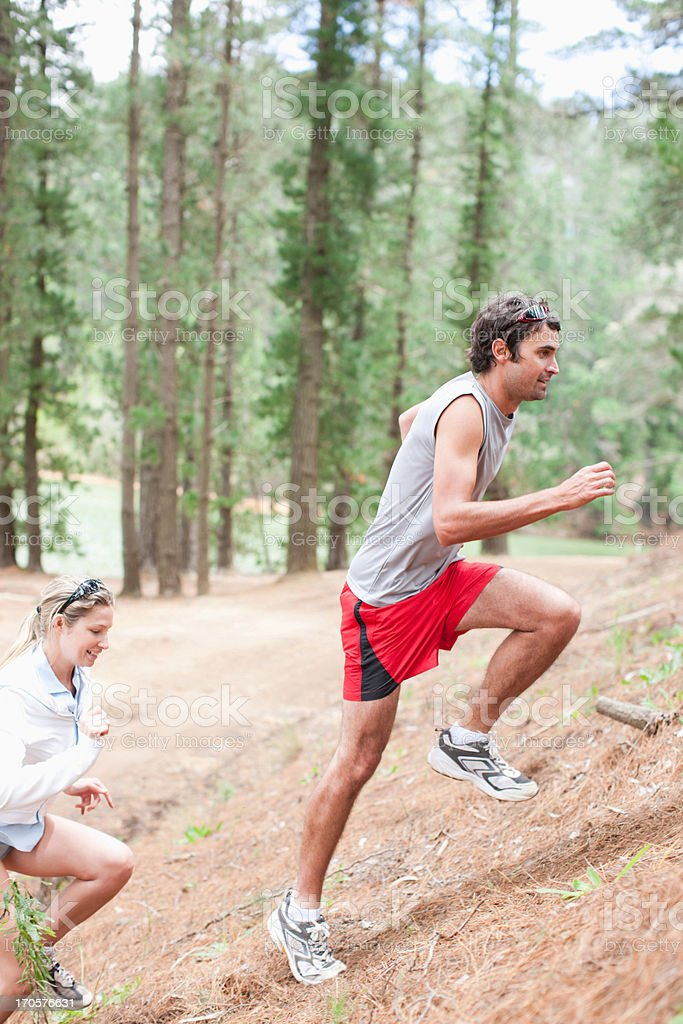 Couple climbing hill in forest royalty-free stock photo