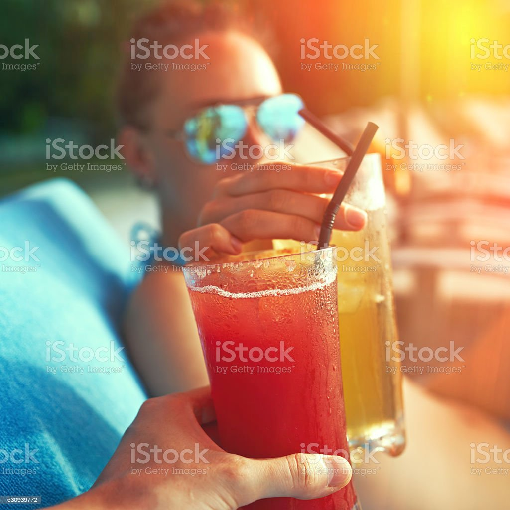 Couple clinking glasses with cocktails stock photo