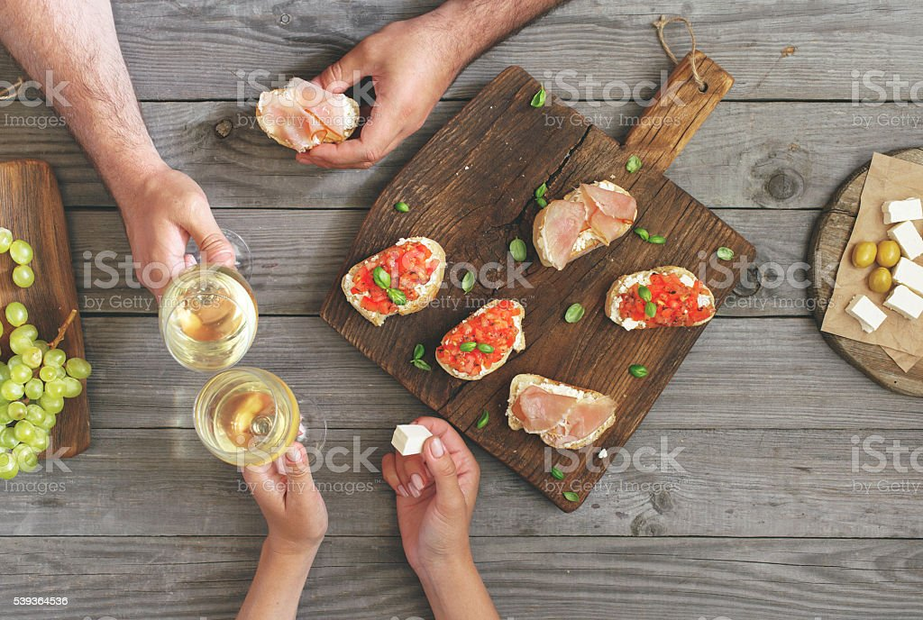 Couple clinking glasses with white wine stock photo
