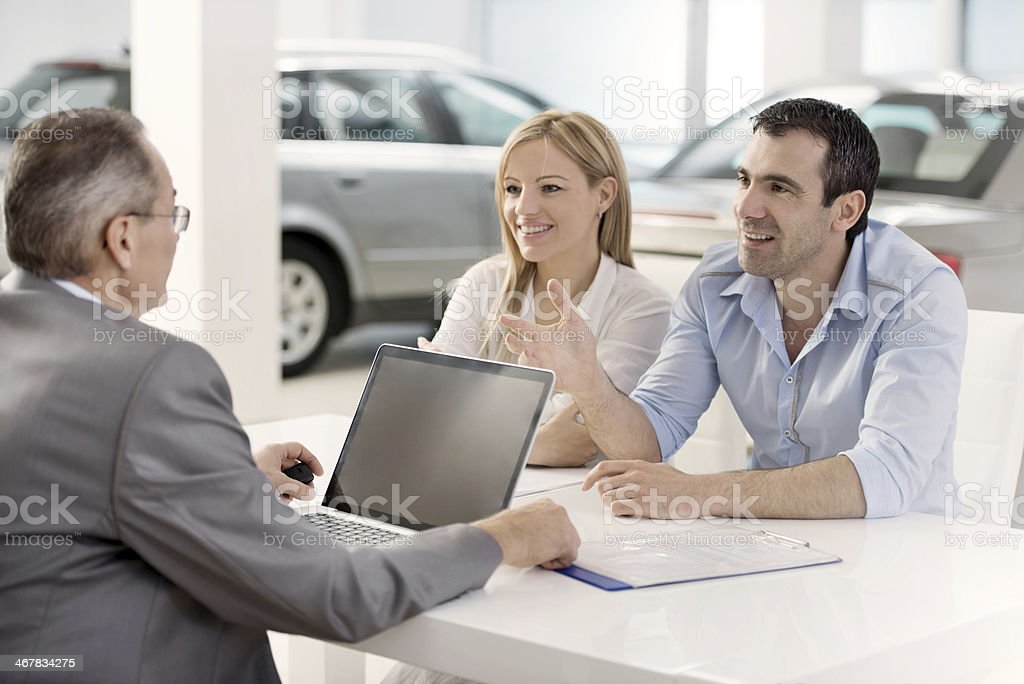 Couple communicating with a car salesperson. stock photo