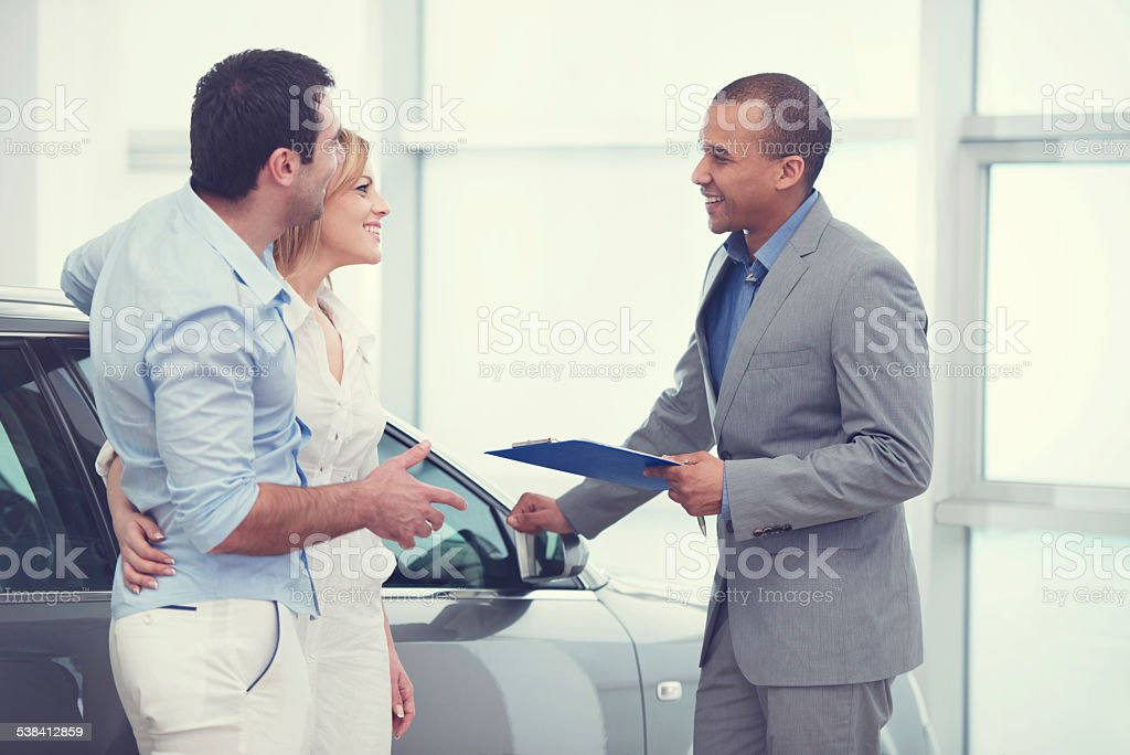 Couple communicating with car sales person. stock photo