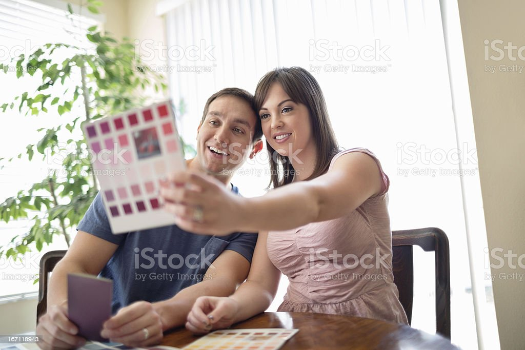 Couple Comparing Color Swatch At Table stock photo