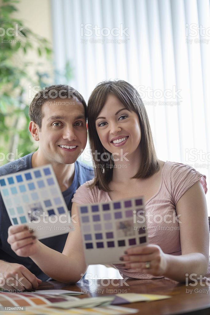 Couple Comparing Color Swatches At Table stock photo