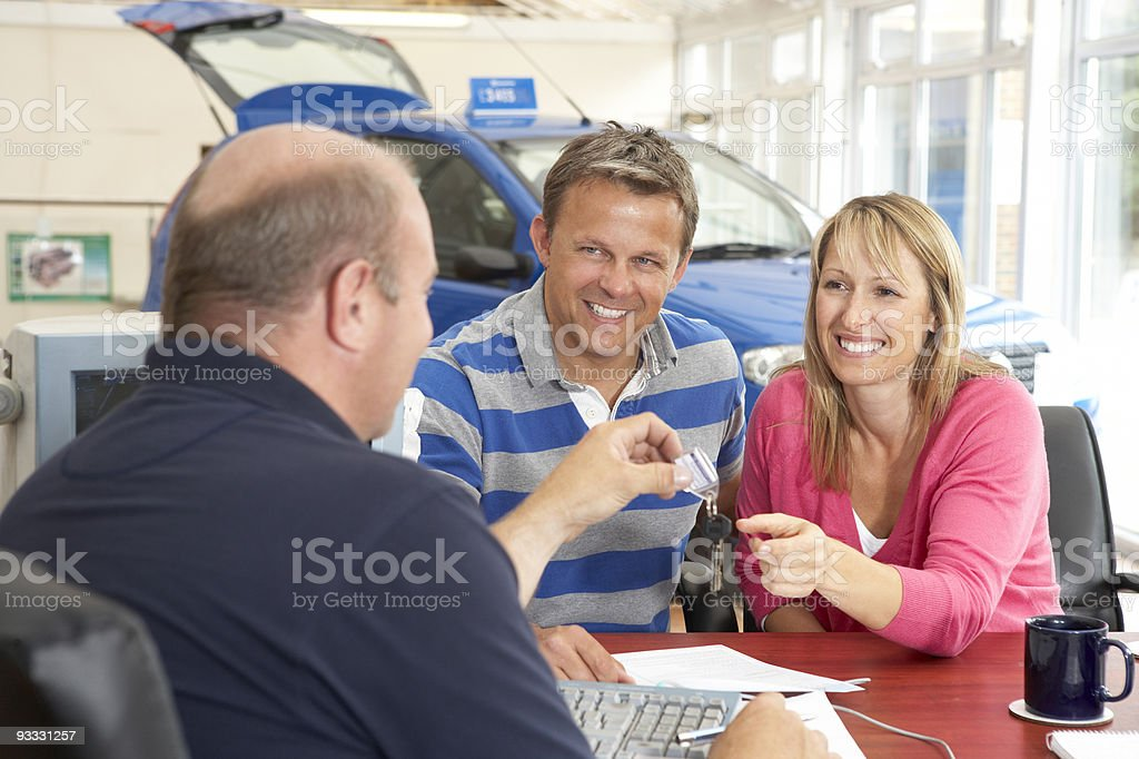 Couple completing paperwork in car showroom royalty-free stock photo