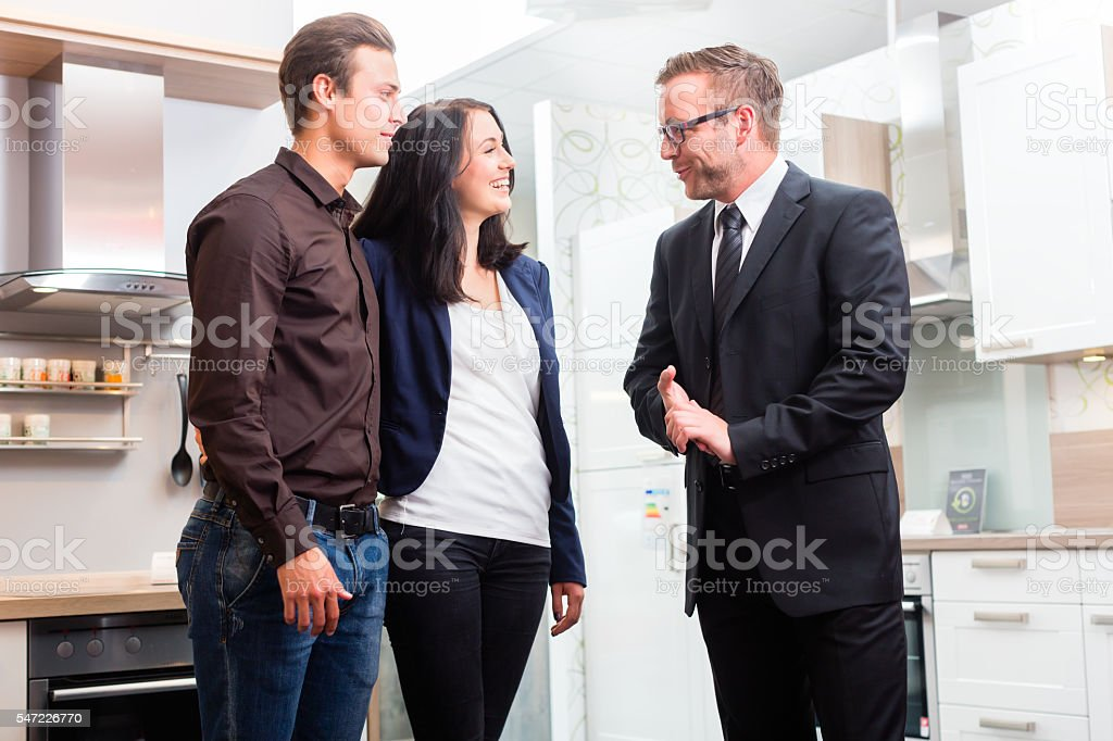 Couple consult salesman for domestic kitchen stock photo