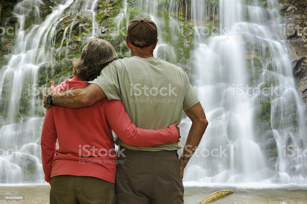 Couple contemplating waterfall royalty-free stock photo