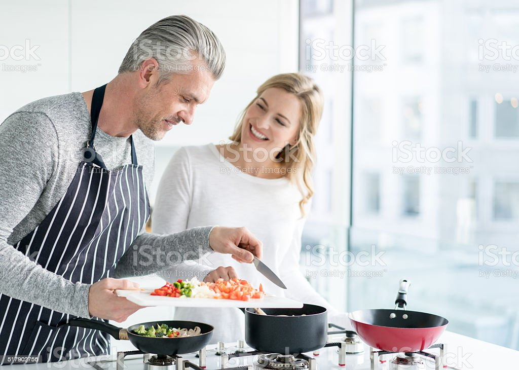 Couple cooking at home stock photo