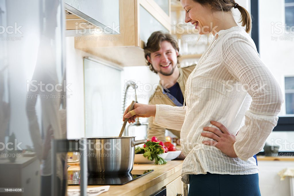 Couple cooking dinner in kitchen, woman stirring pot stock photo
