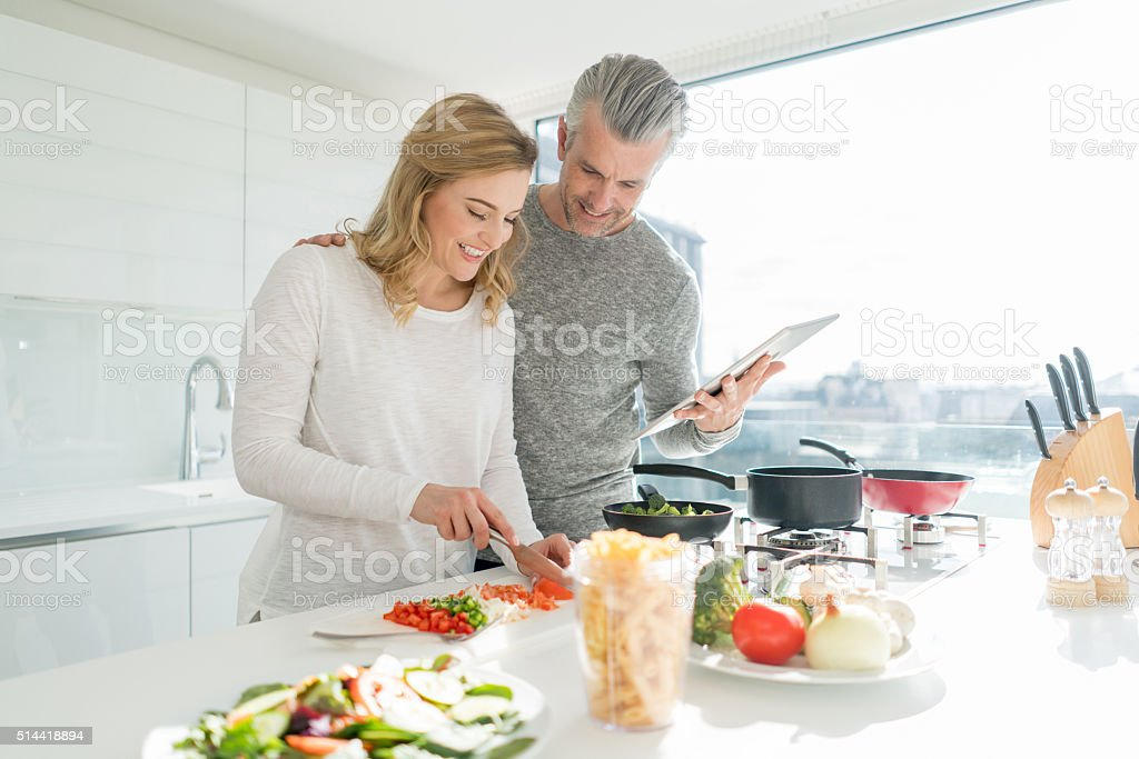 Couple cooking dinner together stock photo