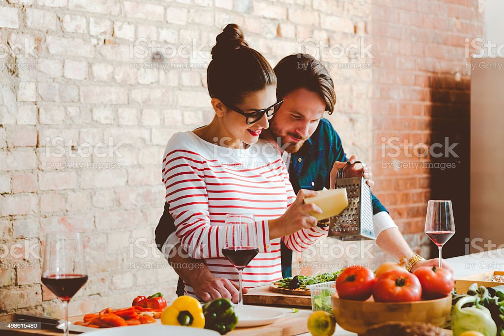 Couple cooking in the modern kitchen, preparing pizza stock photo