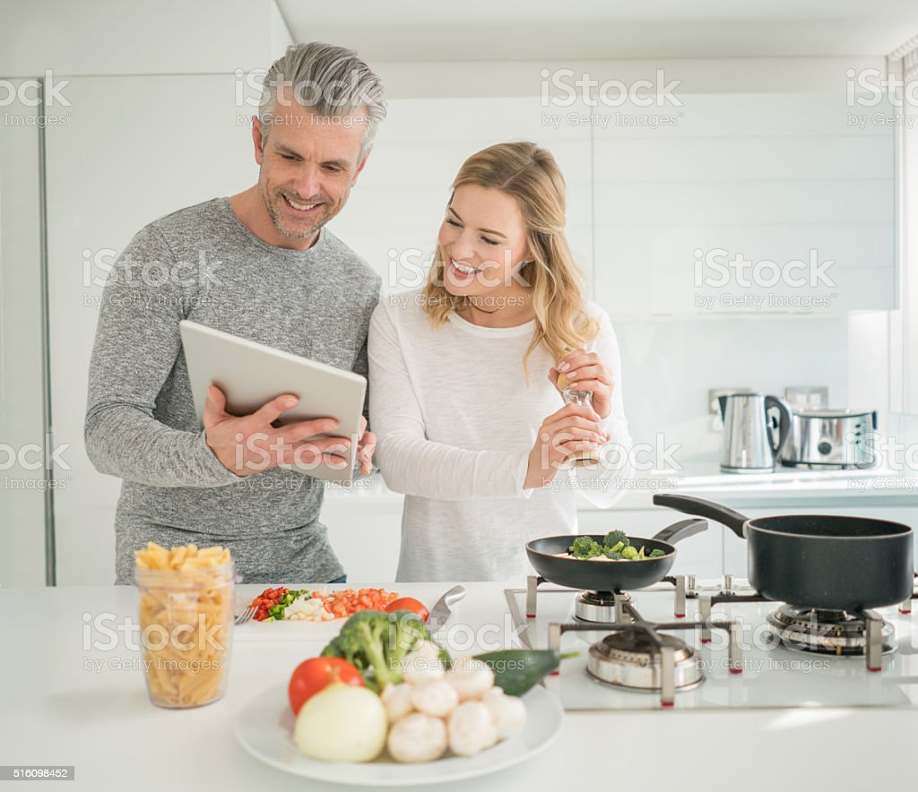 Couple cooking together at home stock photo