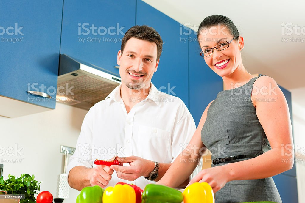 Couple cooking together in kitchen royalty-free stock photo