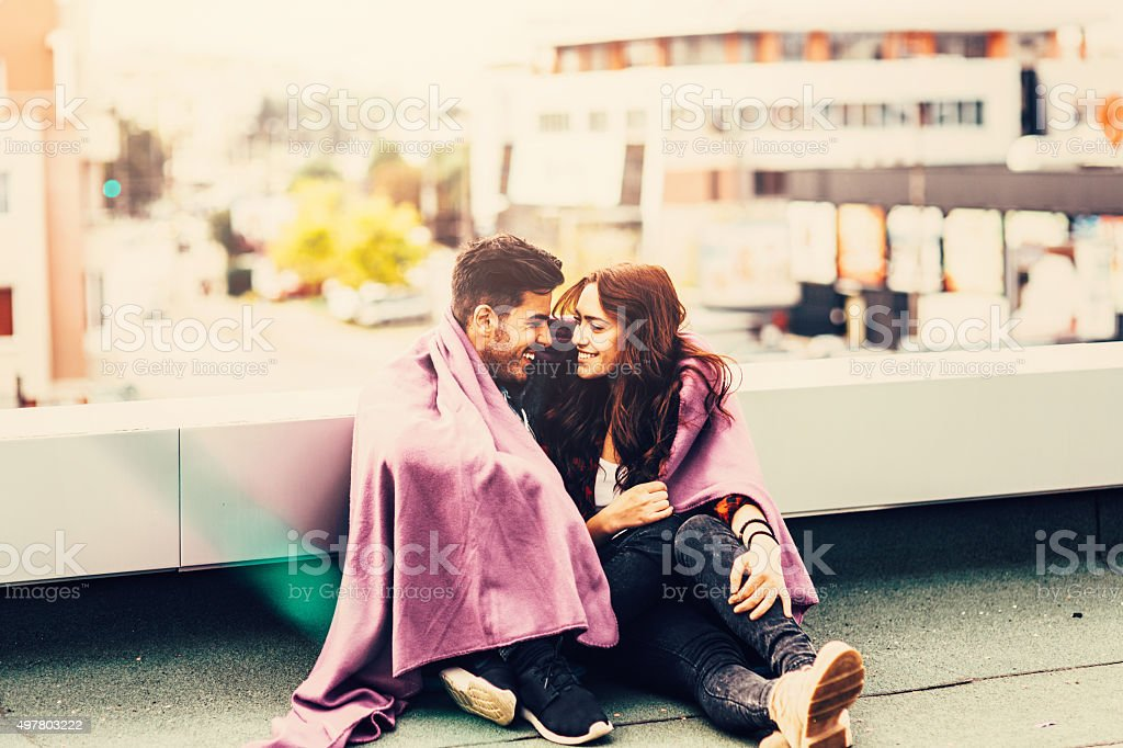 Couple covered up with a blanket stock photo