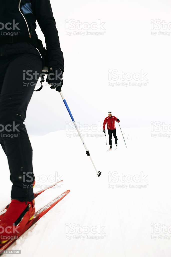 Couple cross-country skiing in snow stock photo