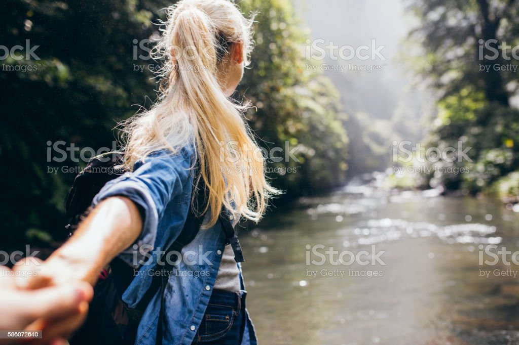 Couple crossing the creek holding hands stock photo