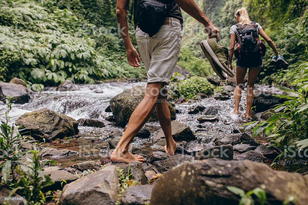 Couple crossing the stream barefooted stock photo