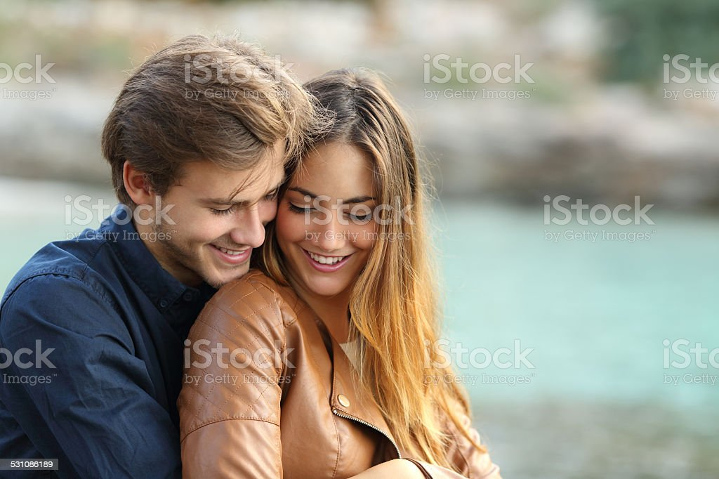 Couple cuddling affectionate on the beach stock photo