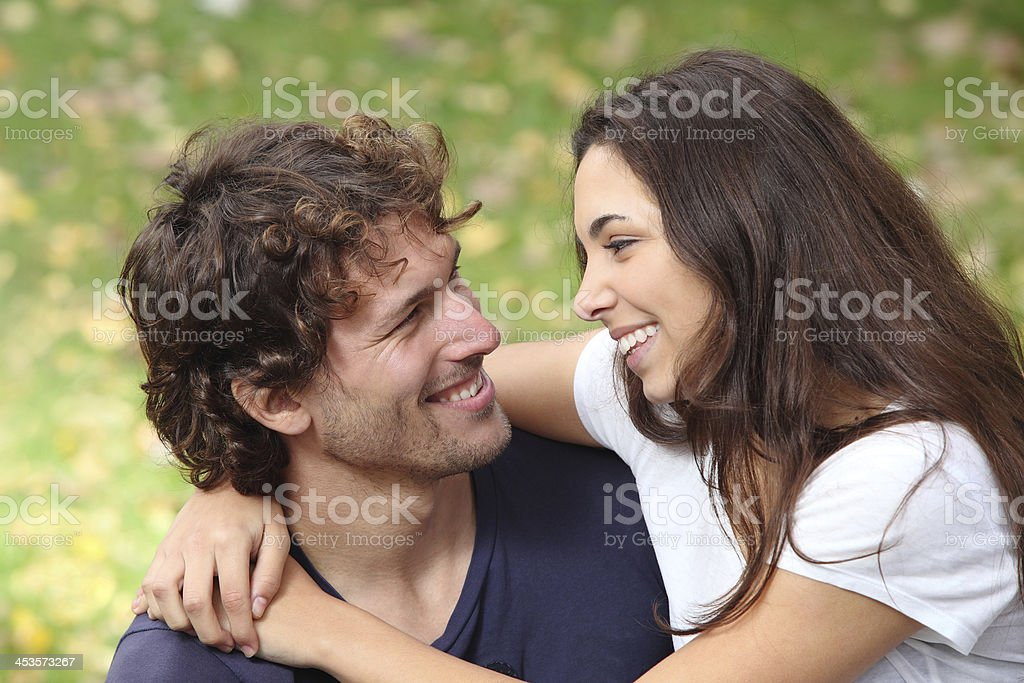 Couple cuddling and flirting in a park stock photo