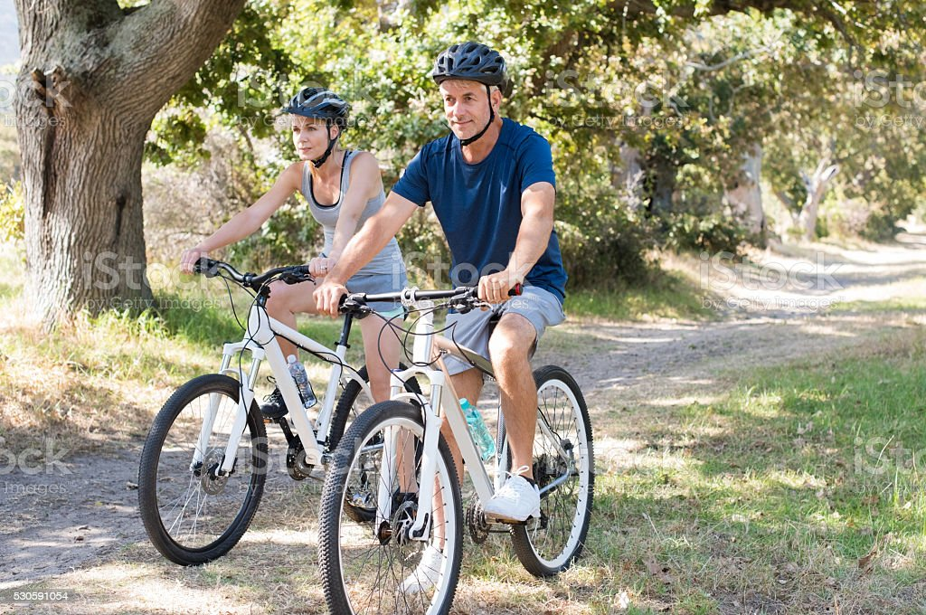 Couple cycling at park stock photo