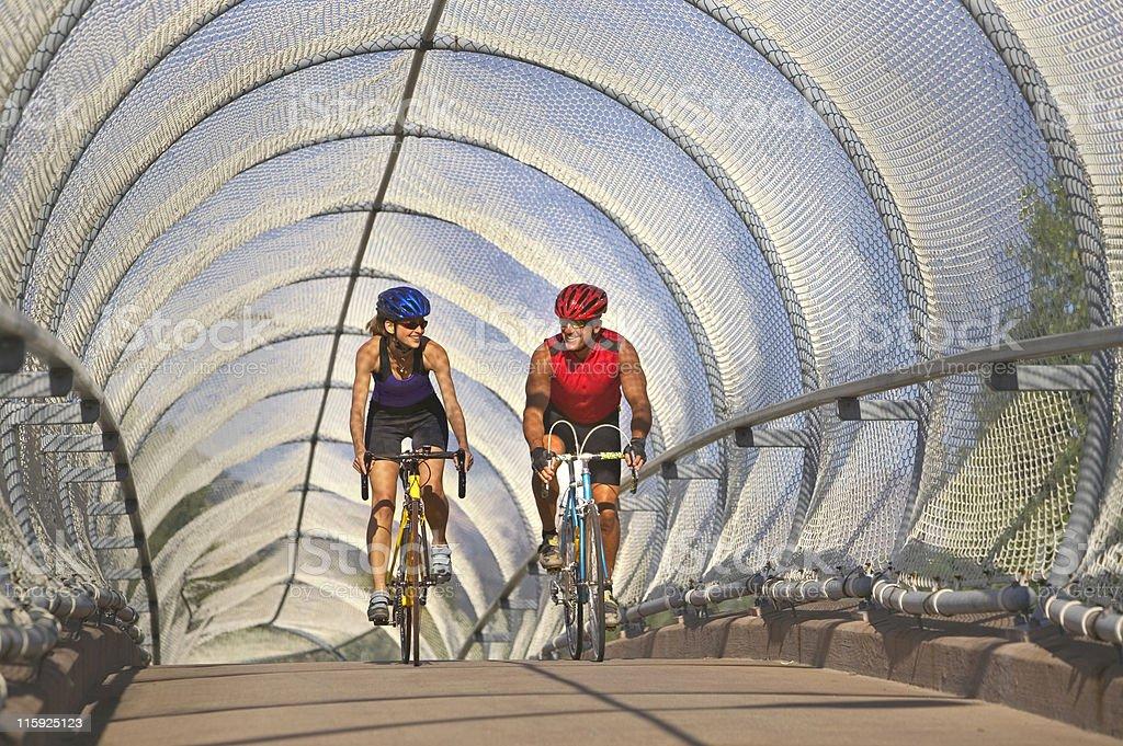 Couple cycling on bridge royalty-free stock photo