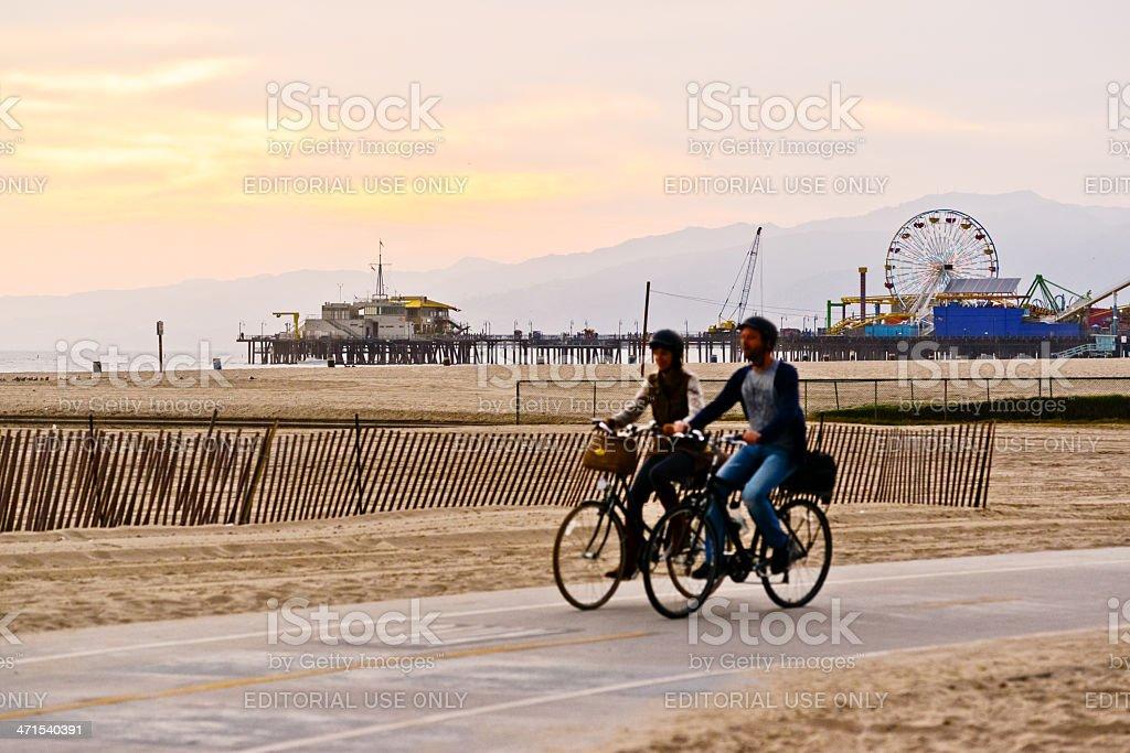 Couple cycling on Santa Monica beach royalty-free stock photo