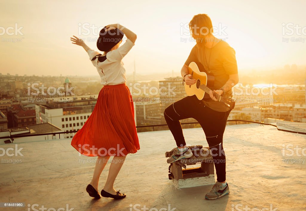 couple dancing on the roof playing the guitar on sunset stock photo