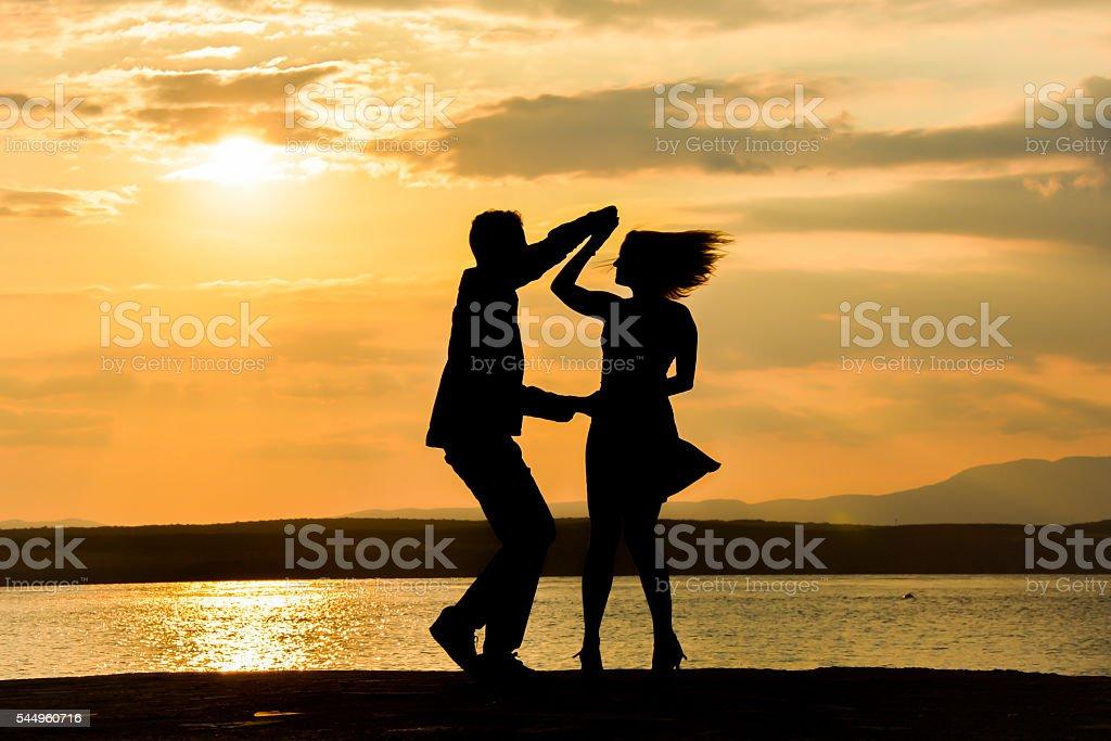 Couple dancing salsa at sunset stock photo