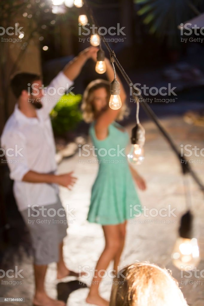 Couple dancing under string lights, focus on light stock photo
