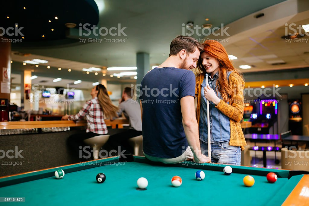 Couple dating and playing snooker stock photo