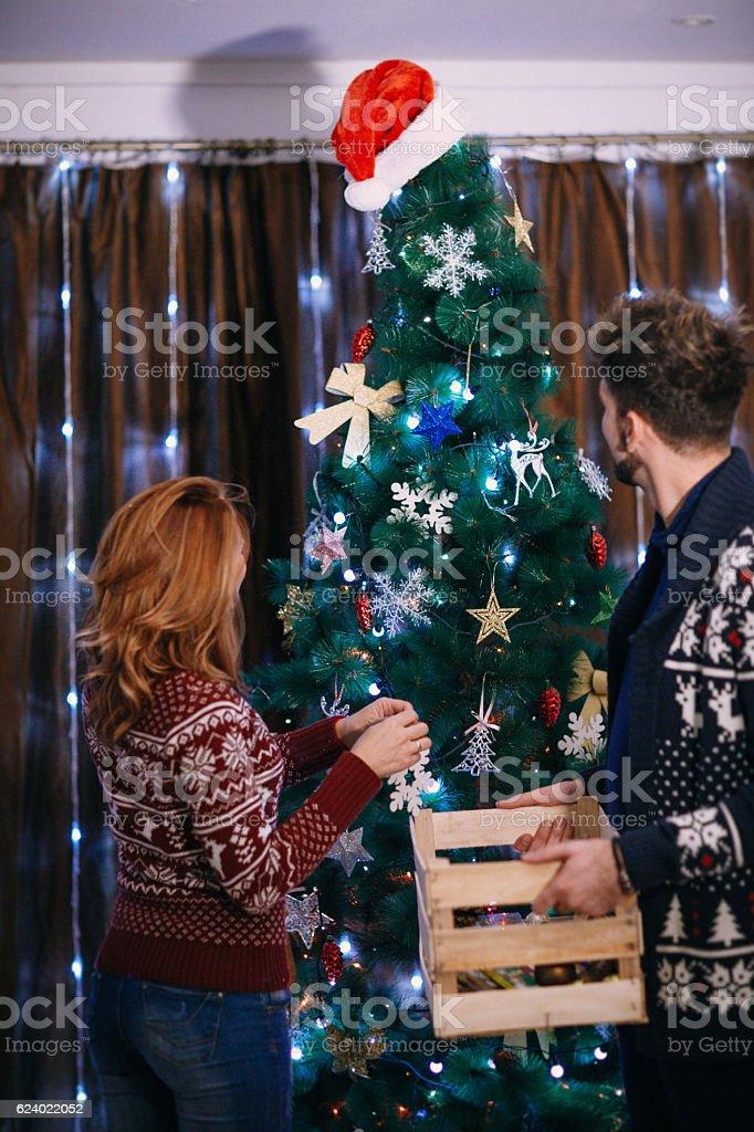 Couple decorating Christmas tree stock photo