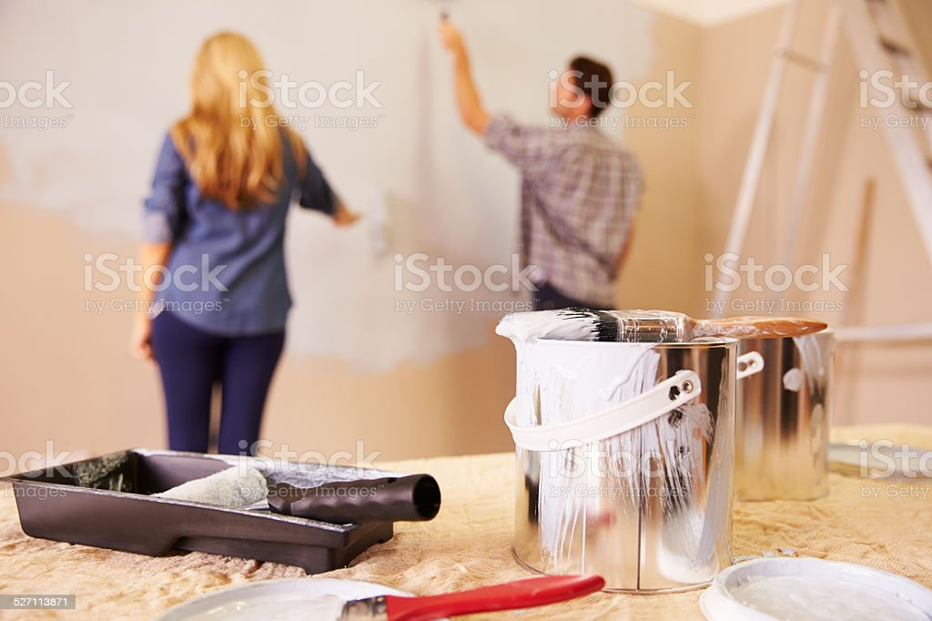 Couple Decorating Room Using Paint Rollers On Wall stock photo