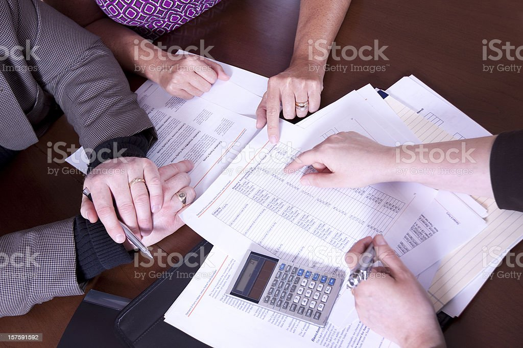 Couple discussing financial matters with advisor - overhead stock photo