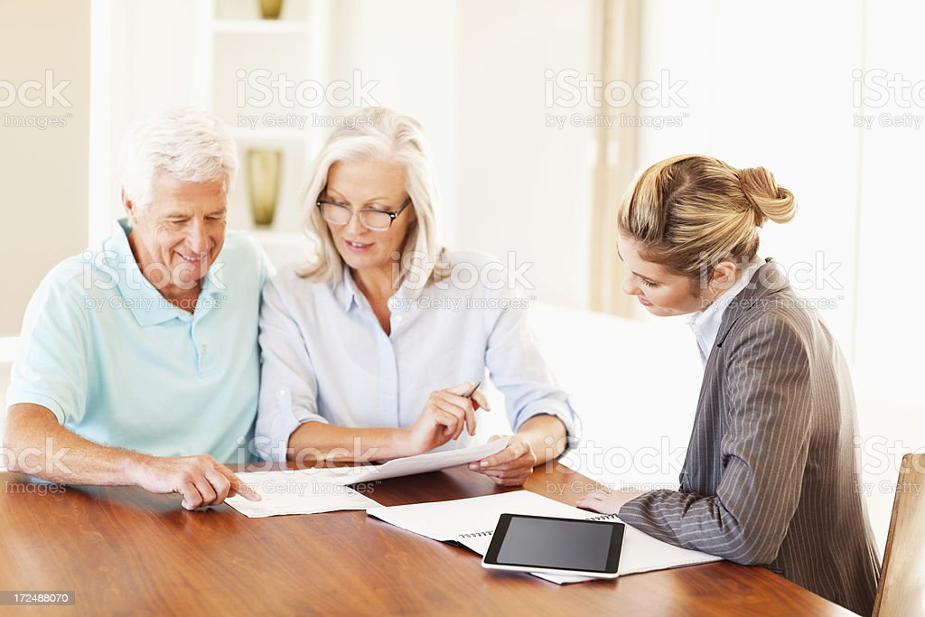 Couple Discussing Paperwork With Financial Consultant royalty-free stock photo